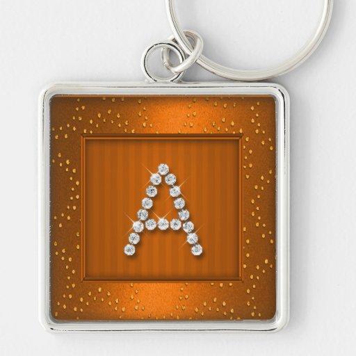 Reflejo y chispa anaranjados con el monograma llavero cuadrado plateado