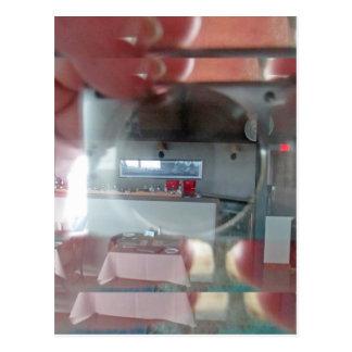 reflexión de la cámara y de la mano en una ventana postales