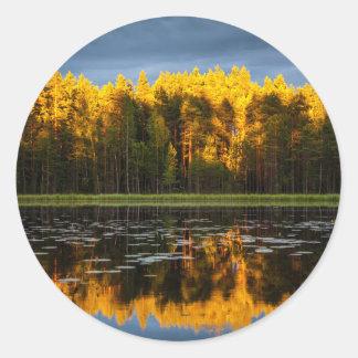 Reflexión de un bosque en una charca pegatina redonda