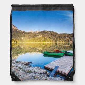 Reflexión en el agua de los lagos y de los barcos  mochilas