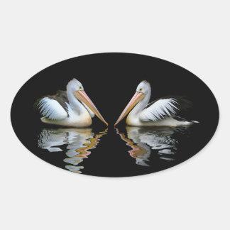 Reflexión hermosa de los pelícanos en fondo negro pegatina ovalada