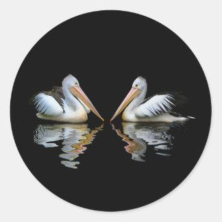 Reflexión hermosa de los pelícanos en fondo negro pegatina redonda