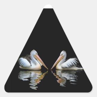 Reflexión hermosa de los pelícanos en fondo negro pegatina triangular
