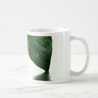 Reflexión verde de la hoja en tema del agua taza de café