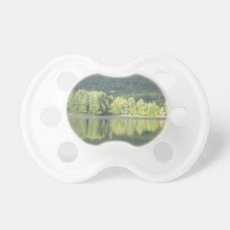 Reflexión verde de los árboles del lago chupetes de bebe