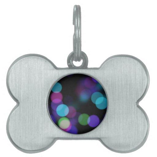 Reflexiones coloreadas púrpuras y verdes azules de placas de nombre de mascota