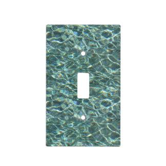 Reflexiones cristalinas de la superficie del agua cubierta para interruptor