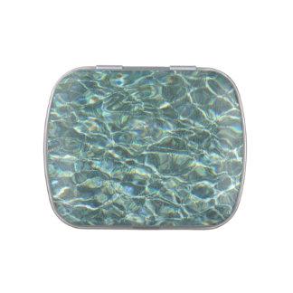 Reflexiones cristalinas de la superficie del agua latas de caramelos