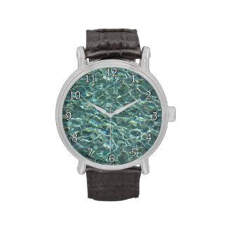 Reflexiones cristalinas de la superficie del agua relojes de mano