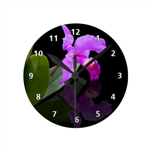 Reflexiones de la orquídea en el reloj negro