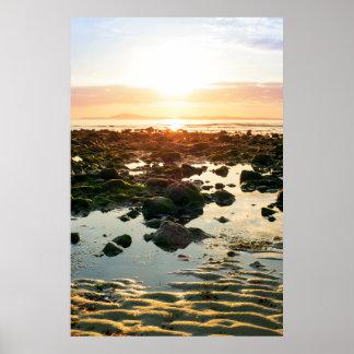 reflexiones serenas en la playa beal rocosa póster
