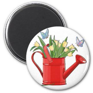 Regadera roja brillante con los tulipanes amarillo iman