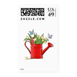 Regadera roja brillante con los tulipanes envio