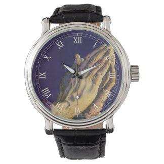 Religión del vintage, manos que ruegan hacia cielo relojes