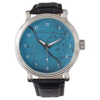 Reloj agrietado azul del fondo de la pared