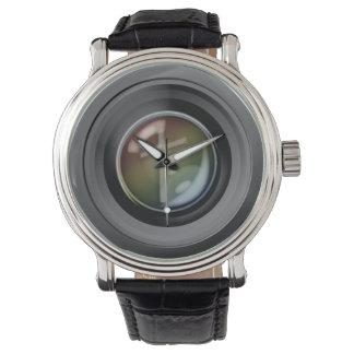 Reloj de la lente de cámara. Foco en Jesús