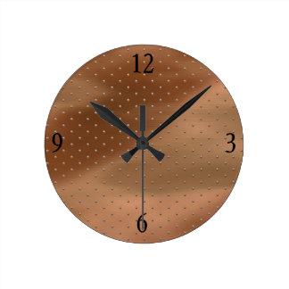 Reloj de pared en las gotas de bronce