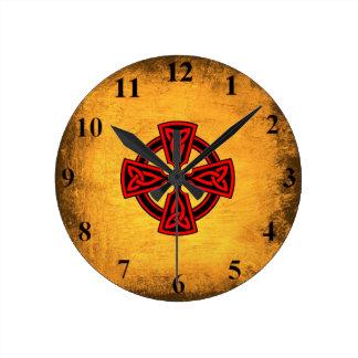 Reloj de pared rojo de la cruz céltica del fondo