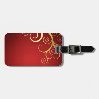 Remolinos de oro en de color rojo oscuro etiquetas maleta