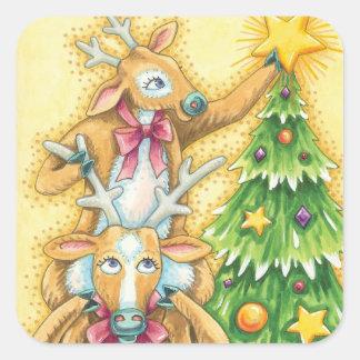 Reno lindo del navidad que pone una estrella en un pegatina cuadrada