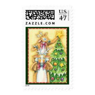Reno lindo del navidad que pone una estrella en un sellos