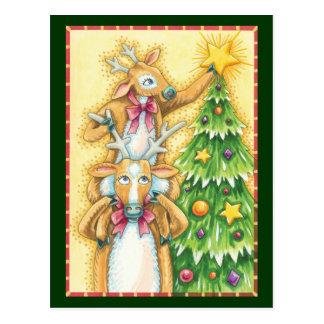 Reno lindo del navidad que pone una estrella en un tarjeta postal
