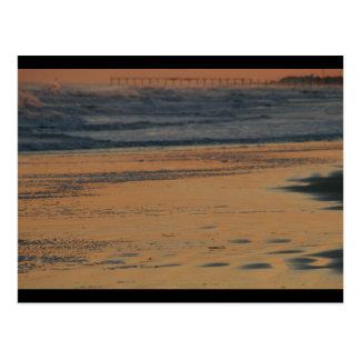 Resplandor de la orilla y puesta del sol del postales