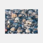 Resplandor subacuático de las piedras de la playa manta de forro polar
