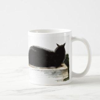 Restos manchados de tinta del gato negro en la taza clásica
