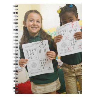 Retrato de dos chicas preescolares con A más y Notebook