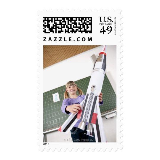 retrato de la chica joven en la tenencia de la timbre postal