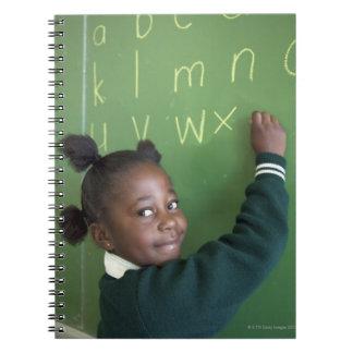 Retrato de la escritura sonriente de la colegiala  libros de apuntes