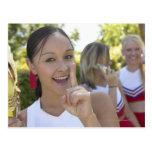 Retrato de una animadora adolescente que sostiene postales