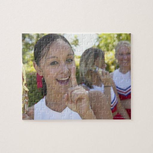 Retrato de una animadora adolescente que sostiene puzzles con fotos