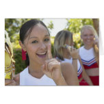 Retrato de una animadora adolescente que sostiene tarjeta de felicitación