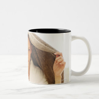 retrato de una mujer joven con una toalla sobre taza de dos tonos