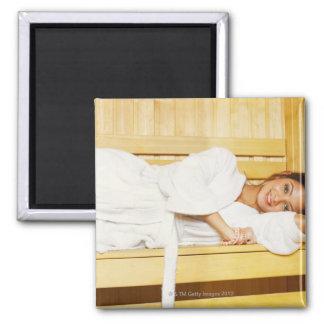 Retrato de una mujer joven que miente en una sauna imán de frigorífico