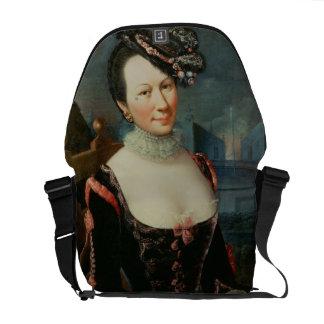 Retrato de una mujer que lleva a cabo una partitur bolsas messenger