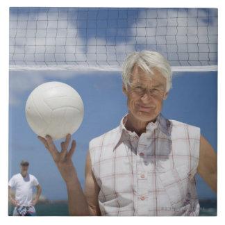Retrato del hombre maduro que sostiene la bola del azulejo cuadrado grande