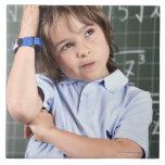 retrato del muchacho joven en sala de clase en pof azulejo cuadrado grande