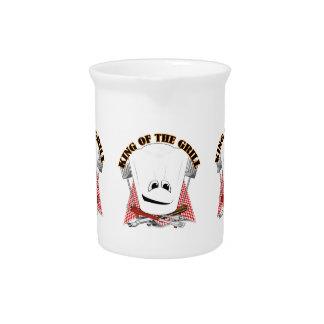 Rey de la parrilla con el gorra del cocinero y las jarra de beber