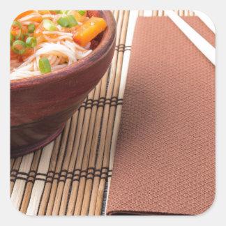 Rice vermicelli hu-teu in a small brown bowl square sticker