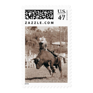 Rider about to fall off bucking bull postage