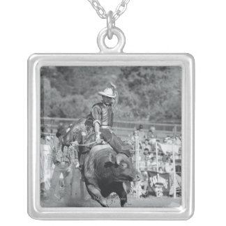 Rider hanging on to bucking bull 2 silver plated necklace