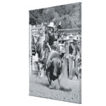 Rider hanging on to bucking bull canvas print