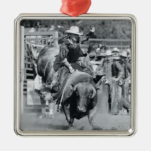 Rider hanging on to bucking bull metal ornament
