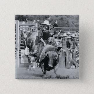 Rider hanging on to bucking bull pinback button