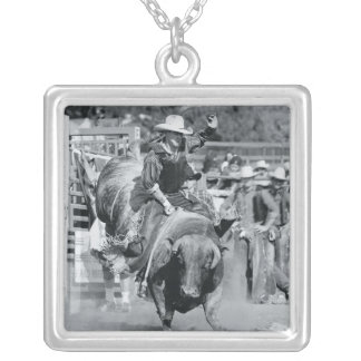Rider hanging on to bucking bull silver plated necklace