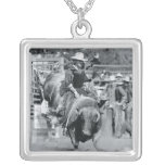 Rider hanging on to bucking bull square pendant necklace