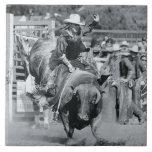 Rider hanging on to bucking bull tile
